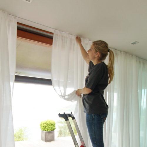 Frau hängt weißen Vorhang auf