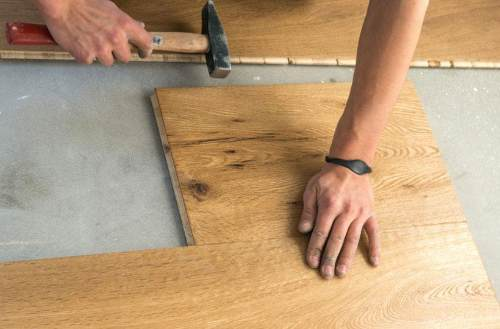 Montage von Parkett per Hand mit Hammer